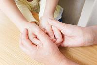 子供の手を握る母とおばあちゃん