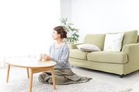 家でコーヒーを飲みくつろぐ女性