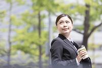 コーヒーを持っているスーツを着た日本人女性