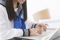 ノートパソコンを操作する女子校生