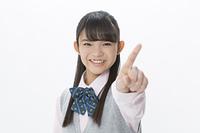 人差し指を立てる女子校生