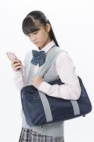 スマートフォンを見る女子校生