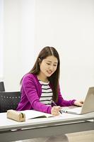 PCを前に勉強する日本人女性
