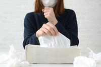 鼻水をかむためにティッシュをとる女性