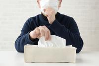 鼻水をかむためにティッシュをとる男性