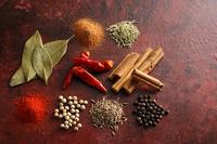 暖色系の背景で撮影した色々なスパイスと香辛料