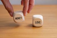 お金のサイコロを持ち上げる手 愛とお金