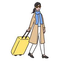 スーツケースを持って歩いている若い女性