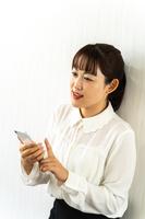 スマートフォンを使う女性社員