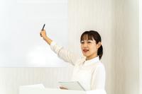 ホワイトボードの前で講義をする女性講師