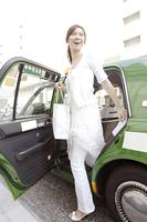 タクシーから降りる女性