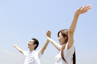 空に向かって両手を上げるカップル
