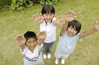 両手を挙げる子供
