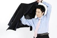 スーツの上着を着るビジネスマン