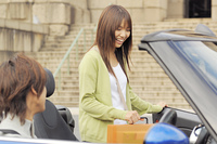 オープンカーの助手席に乗り込む女性
