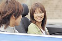 オープンカーの車内で会話するカップル