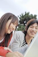 ノートパソコンを覗く大学生カップル