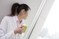 コーヒーカップを持ち外を眺めるビジネスレディ