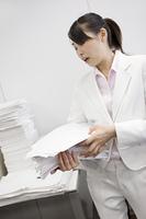 大量の紙を整理するビジネスレディ