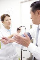 男性患者の血圧を測る看護師