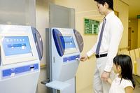 診察カードを自動受付機に入れる男性と女の子