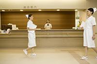 病院の受付前を歩く看護師