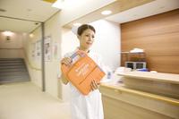 除細動器を運ぶ看護師