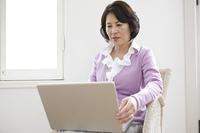 ノートパソコンを開くシニア女性