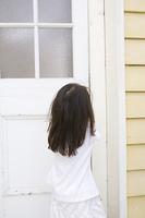 玄関の扉を開けようとする女の子