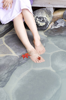 露天風呂に浸かった女性の足と紅葉