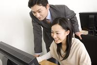 女性にパソコンを教えるスクール講師