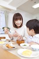 朝食時にご飯を食べる母親と息子