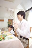 朝食時に「頂きます。」をする父親と娘