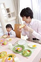 トーストを食べる男性と女の子