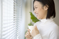 コーヒーカップを持って外を眺める女性