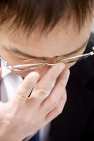 メガネを押さえるビジネスマン
