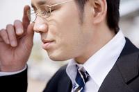 メガネをかけ直すビジネスマン