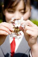 桜の花びらを手に持つ女子高生