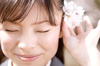桜の花びらを頭に添える女子高生
