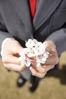 桜の花を持つ女子高生の手元