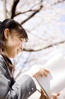 桜の下で本を読む女子高生