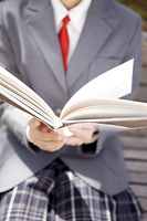 ベンチで本を読む女子高生の手元