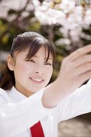 桜に触れようとする女子高生