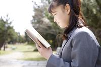 ベンチで本を読む女子高生