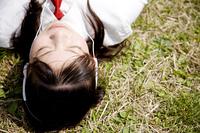 芝生に寝転がりながら音楽を聴く女子高生