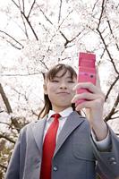 桜の下で記念写真を撮る女子高生