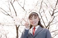 桜の下でピースをする女子高生