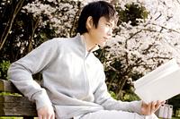 ベンチで本を読む男性