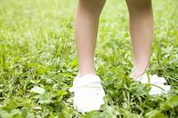 芝生の上に立つ女の子の足元