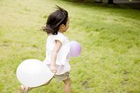 風船を持って駆け回る女の子